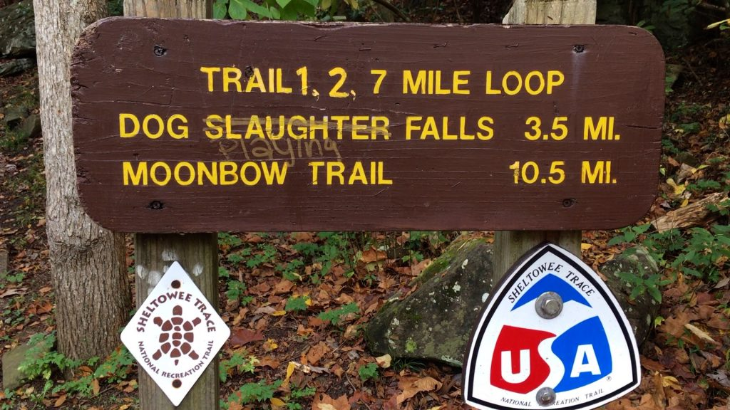 A sign that appears just north of the Cumberland Falls on the Moonbow Trail. Sign reads: TRAIL 1, 2, 7 MILE LOOP; DOG SLAUGHTER FALLS 3.5 MI.; MOONBOW TRAIL 10.5 MI. Someone has tried to scrawl through the word 'slaughter' and replace it with the word 'playing'