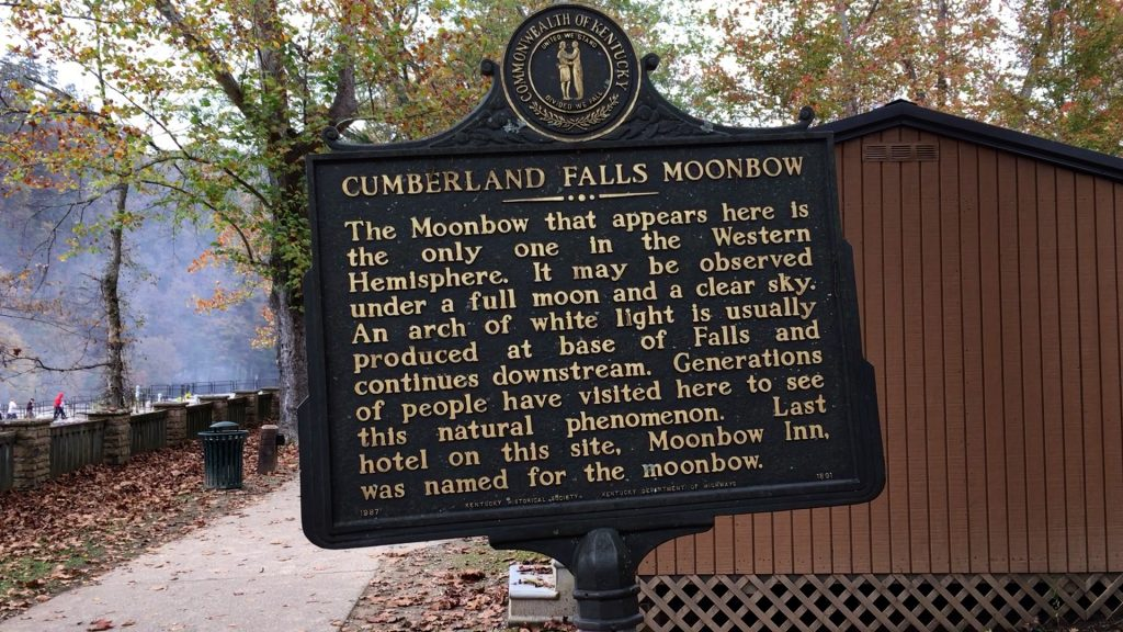 Large plaque describing the Cumberland Falls Moonbow: The Moonbow that appears here is the only one in the Western Hemisphere. It may be observed under a full moon and a clear sky. An arch of white light is usually produced at base of Falls and continues downstream. Generations of people have visited here to see this natural phenomenon. Last hotel on this site, Moonbow Inn, was named for the moonbow.